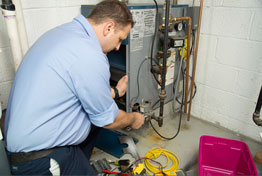 technician fixing a furnace