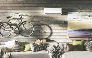 Modern room with wall art and bike hanging above couch with ductless split system