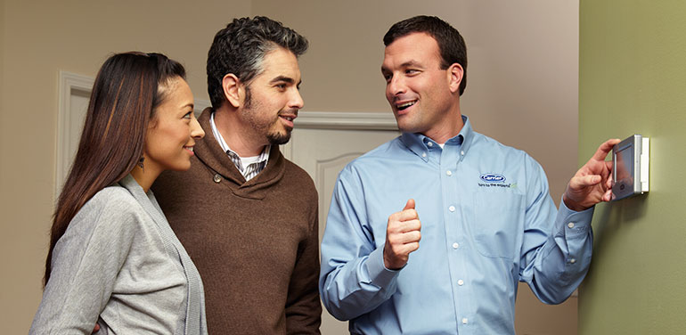 HVAC technician showing a couple the features of their new smart thermostat